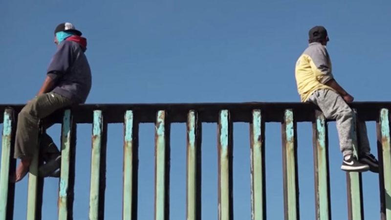 Videos: Ante la mirada de la migra, decenas de migrantes centroamericanos escalan la valla fronteriza de Tijuana