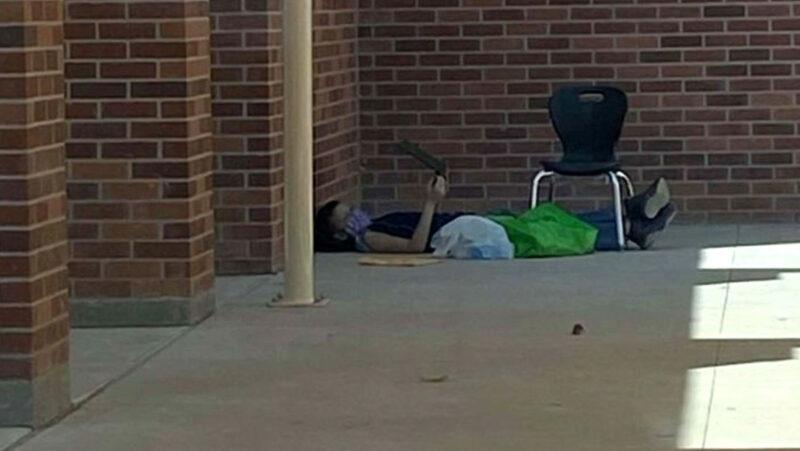 De familia pobre, un niño se sienta todo el día frente a su escuela para conectarse a Internet y atender a las clases virtuales